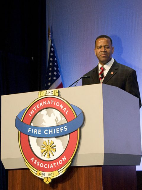 Kelvin Cochran, former Atlanta fire chief, speaks at the podium after being sworn in at the annual convention of International Fire Chiefs in Dallas, Tex., on August 27, 2009.