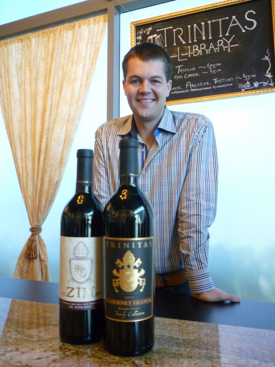 Garrett Busch, CEO of Napa Valley's Trinitas Winery, with two wines that honor popes - RatZINger Zinfandel and Cabernet FRANCis. Religion News Service photo by Kimberly Winston