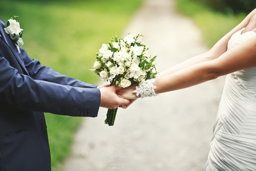 A bride and groom hold hands.