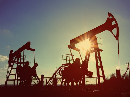 Two working oil pumps are silhouetted against the sky.
