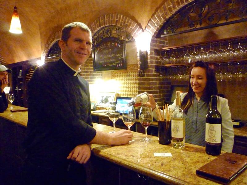 "Father Jonathan Meyer tastes Trinitas Winery's ""Faith Collection"" wines as Rebekah Allen pours. Religion News Service photo by Kimberly Winston"