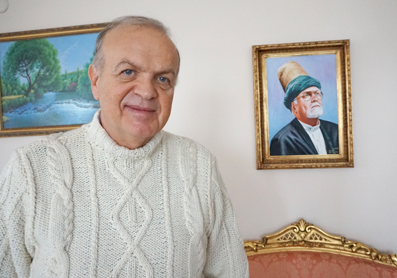 Faruk Hemdem Celebi is a 22nd generation descendant of Rumi and president of the International Mevlana Foundation. Behind him hangs a picture of his father and predecessor as the alleged hereditary leader of the Mevlevi order. Religion News Service photo by Michael Kaplan