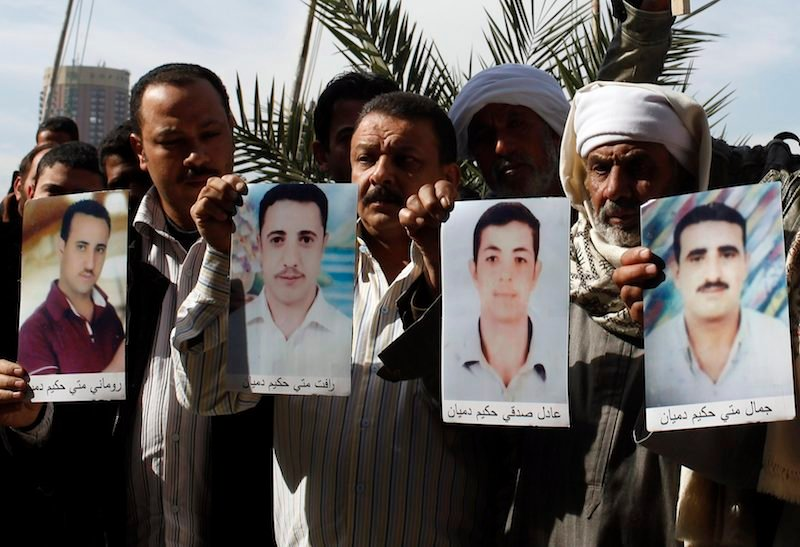 Families of the 27 Egyptian Coptic Christians workers kidnapped in the Libyan city of Sirte, hold pictures of their kidnapped relatives as they ask for their release, in front of the U.N. office in Cairo January 19, 2015. Photo by REUTERS/Asmaa Waguih