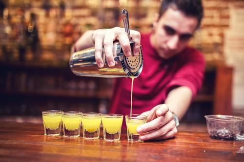 A bartender pours shots.