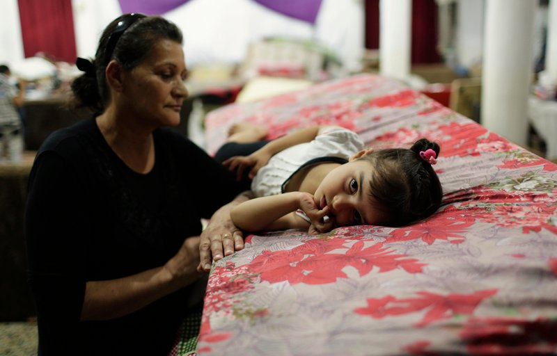 Displaced people from the minority Yazidi sect, who fled violence in the Iraqi province of Nineveh Plain in northern Iraq, take shelter at Margurgis Church in Dohuk on August 20, 2014. Photo courtesy of REUTERS/Youssef Boudlal  *Editors: This photo may only be republished with RNS-ASSYRIANS-ISIS, originally transmitted on February 24, 2015.
