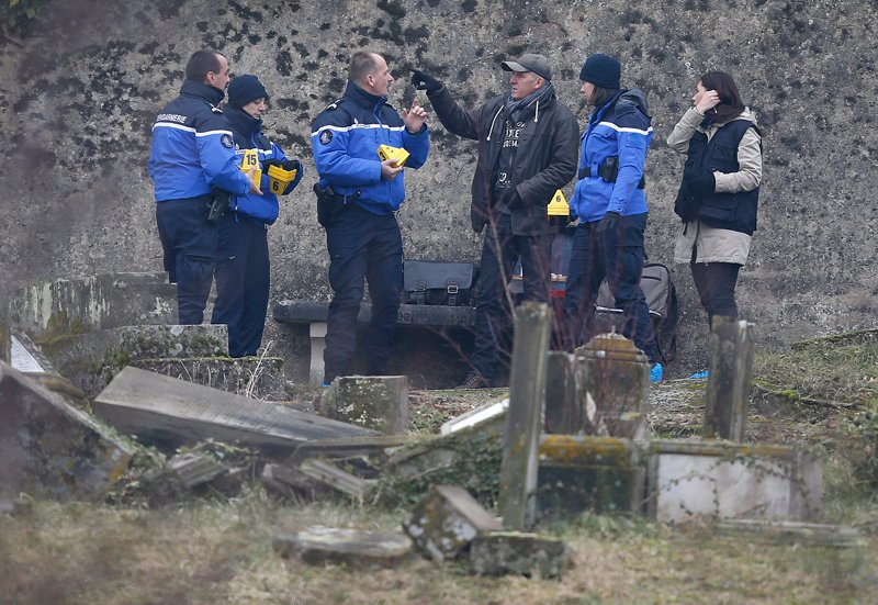 French gendarmes investigate near desecrated tombstones at the Sarre-Union Jewish cemetery in eastern France on February 16, 2015. Several hundreds Jewish tombs have been damaged in a cemetery near the northeastern French city of Strasbourg, the French interior minister said on Sunday. Photo courtesy of REUTERS/Vincent Kessler  *Editors: This photo may only be republished with RNS-CEMETERY-DESECRATE, originally transmitted on February 16, 2015