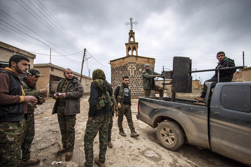 Fighters of the Kurdish People's Protection Units (YPG) stand near a pick-up truck mounted with an anti-aircraft weapon in front of a church in the Assyrian village of Tel Jumaa, north of Tel Tamr town February 25, 2015. Kurdish militia pressed an offensive against Islamic State in northeast Syria on Wednesday, cutting one of its supply lines from Iraq, as fears mounted for dozens of Christians abducted by the hardline group. The Assyrian Christians were taken from villages near the town of Tel Tamr, some 20 km (12 miles) to the northwest of the city of Hasaka. There has been no word on their fate. There have been conflicting reports on where the Christians had been taken. Photo courtesy of REUTERS/Rodi Said *Editors: This photo may only be republished with RNS-CHRISTIANS-SYRIA, originally transmitted on February 26, 2015.