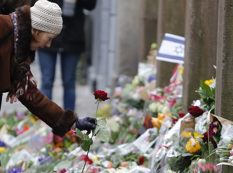A woman lays down a flower at a memorial for the victims of the deadly attacks in front of the synagogue in Krystalgade in Copenhagen, on February 16, 2015. Photo courtesy of REUTERS/Leonhard Foeger *Editors: This photo may only be republished with RNS-DENMARK-SHOOTING, originally transmitted on RNS-DENMARK-SHOOTING.