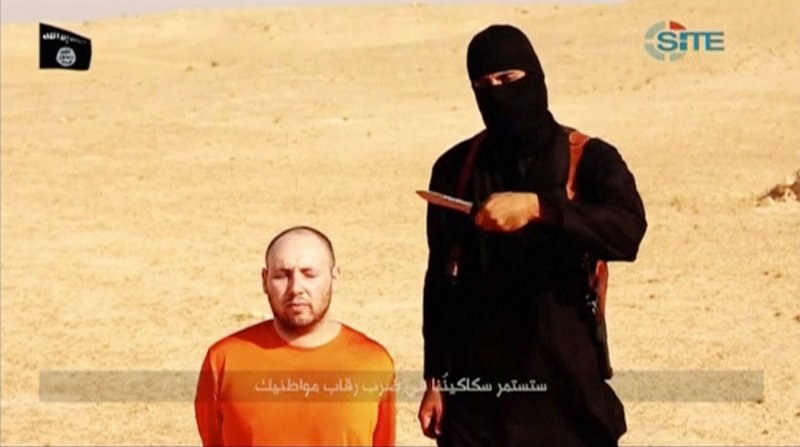 A masked, black-clad militant, who has been identified by the Washington Post newspaper as a Briton named Mohammed Emwazi, stands next to a man purported to be Steven Sotloff in this still image from a video obtained from SITE Intel Group website February 26, 2015. Photo courtesy of REUTERS *Editors: This photo may not be republished.