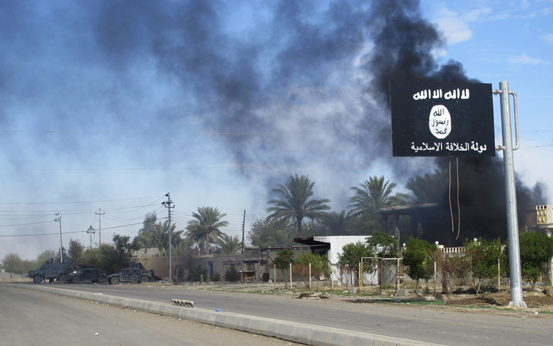 Smoke raises behind an Islamic State flag after Iraqi security forces and Shiite fighters took control of Saadiya in Diyala province from Islamist State militants on November 24, 2014. Photo courtesy of REUTERS/Stringer  *Editors: This photo may only be republished with RNS-ISIS-WEST, originally transmitted on February 23, 2015.