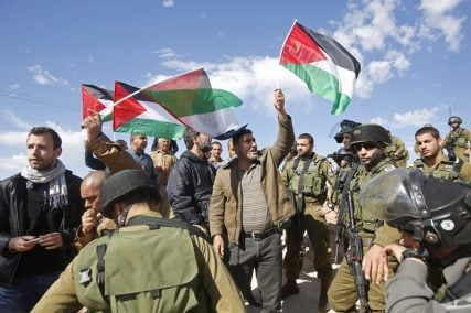 Protesters hold Palestinian flags as they stand next to Israeli soldiers and border policemen during a protest against Jewish settlements in Jabaa, south of the West Bank city of Bethlehem on February 7, 2015. Photo courtesy of REUTERS/Mussa Qawasma  *Editors: This photo may only be republished with RNS-MOSQUE-ARSON, originally transmitted on February 25, 2015.