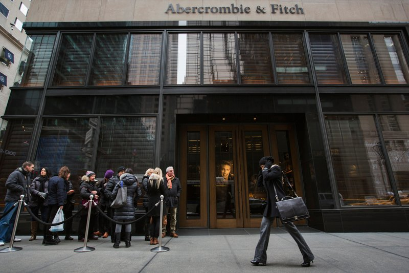 A pedestrian walks past shoppers lined up to wait for the opening of an Abercrombie & Fitch store in New York on November 26, 2013. Photo courtesy of REUTERS/Lucas Jackson  *Editors: This photo may only be republished with RNS-SCOTUS-HEADSCARF, originally transmitted on February 19, 2015.