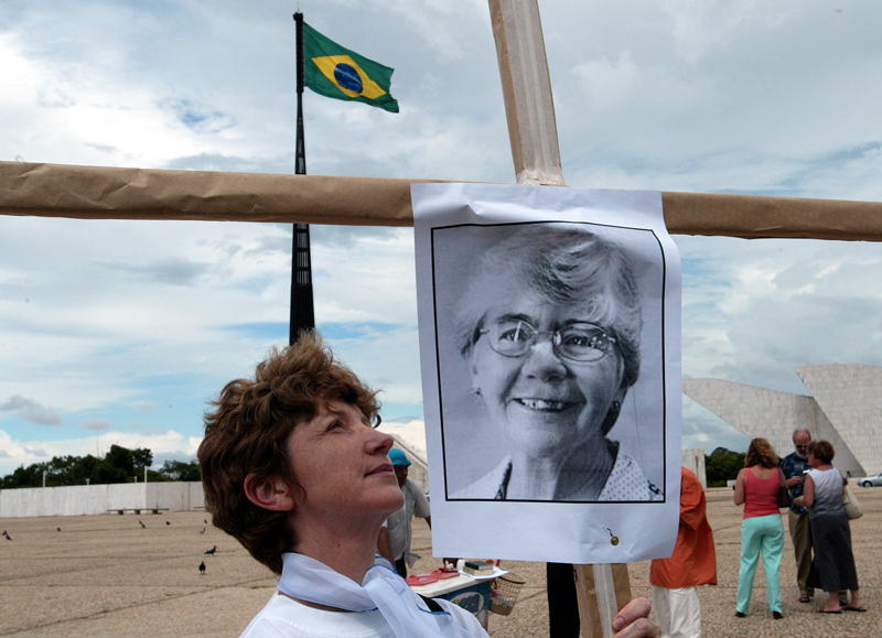 Members of the Brazilian National Conference of Catholic Bishops protest against the death of American nun Stang. Sister Delci Fauzen of the National Conference of Catholic Bishops (CNBB) carry a cross with a portrait of American nun Dorothy Stang during a protest against her death, in front of Brazil's Supreme Court in Brasilia, on February 18, 2005. Photo courtesy of REUTERS/Jamil Bittar *Editors: This photo may only be republished with RNS-STANG-LEGACY, originally transmitted on February 12, 2015.