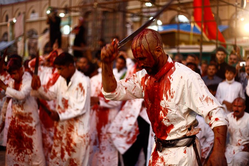 Iraq Shi'ite Muslim men bleed as they gash their foreheads with swords and beat themselves during the religious festival of Ashura in Najaf, 160km (100 miles) south of Baghdad on November 13, 2013. During Ashura, Shi'ite Muslims commemorate the slaying of Prophet Muhammad's grandson Hussein in Kerbala in 680 AD. The most important day in the Shi'ite calendar, Ashura has become a show of strength in Iraq for a majority whose public worship was repressed by former dictator Saddam Hussein. Photo courtesy of REUTERS/Alaa Al-Marjani