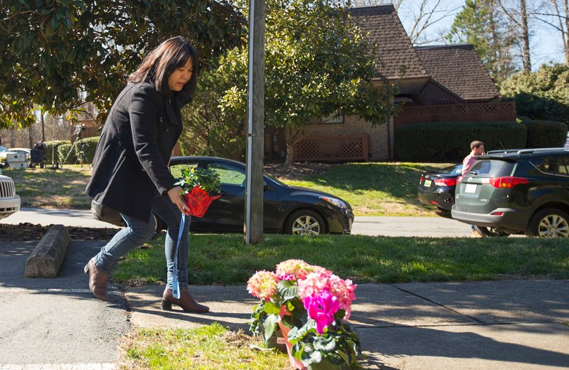 A woman places flowers near a building where three young Muslims were killed on Tuesday, in Chapel Hill, North Carolina on February 11, 2015. Craig Stephen Hicks, the gunman who had posted anti-religious messages on Facebook was charged with killing Deah Shaddy Barakat, his wife Yusor Mohammad and Yusor's sister Razan Mohammad Abu-Salha in what police said on Wednesday was a dispute over parking and possibly a hate crime. Hicks, 46, was arrested and charged with three counts of first-degree murder in the shootings near the University of North Carolina campus. Photo courtesy of REUTERS/Chris Keane *Editors: This photo may only be republished with RNS-UNC-MUSLIMS, originally transmitted on February 11, 2015.