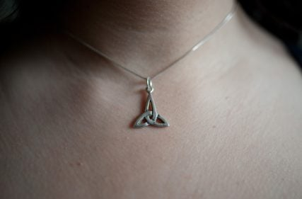 "Nadia Bulkin wears a silver triquetra necklace she bought for herself. She said it is a religious symbol used by both Christianity and paganism. She said ""I personally like it, because it signifies balance. I like the geometric appeal of it. It is also useful when I am questioned by very Christian religious people in Nebraska. They can assume it is the Holy Trinity, and I say, yeah, that's what it is. Triquetra was used in this campy TV show called Charmed, about witches living in San Francisco, and I love the show! That's where I first saw it. It sort of symbolizes my weird relationship with pop spirituality."" Religion News Service photo by Sait Serkan Gurbuz"