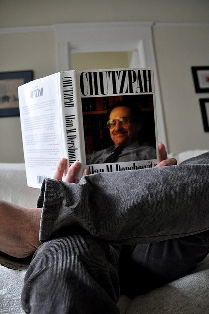 "A person reads Alan Dershowitz' book ""Chutzpah."""