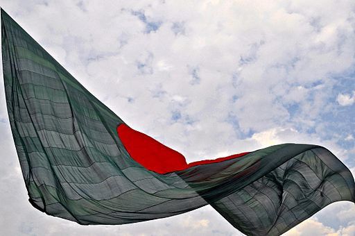 The Bangladesh national flag waves in front of a cloudy sky.