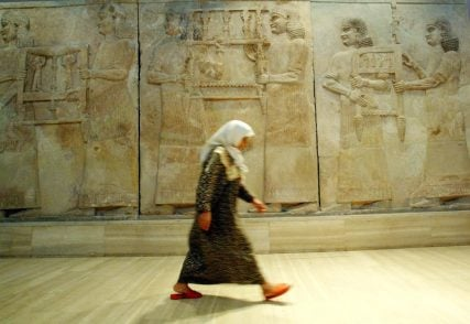 An Iraqi woman walks in front of Assyrian mural sculptures on exhibit in Baghdad in this 2003 photo. One of the most significant archaeological finds of the 20th century, the Nimrud treasures -- excavated in the ancient Assyrian city of Nimrud near present day Mosul-- date back to 900 B.C. and consist of gold artifacts and precious gems.