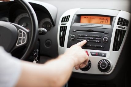A driver changes the car radio station.