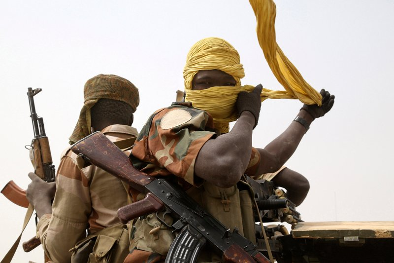 A Chadian soldier fixes his headscarf while driving at the front line during battle against insurgent group Boko Haram in Gambaru on February 26, 2015. Niger, Cameroon and Chad have launched a regional military campaign to help Nigeria defeat the Boko Haram insurgency, which aims to carve an Islamic emirate out of northeastern Nigeria. Photo courtesy of REUTERS/Emmanuel Braun