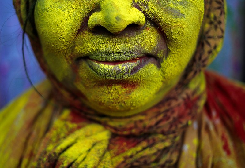 The face of a widow is seen daubed in color after she took part in the Holi celebrations organized by non-governmental organization Sulabh International at a widows' ashram at Vrindavan in the northern Indian state of Uttar Pradesh on March 4, 2015. Traditionally in Hindu culture, widows are expected to renounce earthly pleasure so they do not celebrate Holi. But women at the shelter for widows, who have been abandoned by their families, celebrated the festival by throwing flowers and coloured powder. Holi, also known as the Festival of Colors, heralds the beginning of spring and is celebrated all over India. Photo courtesy of REUTERS/Anindito Mukherjee