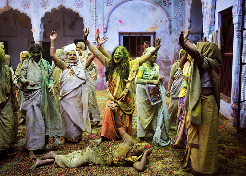 Widows daubed in colors chant religious hymns as they dance during the Holi celebrations organized by non-governmental organization Sulabh International at a widows' ashram at Vrindavan in the northern Indian state of Uttar Pradesh on March 4, 2015. Photo courtesy of REUTERS/Anindito Mukherjee