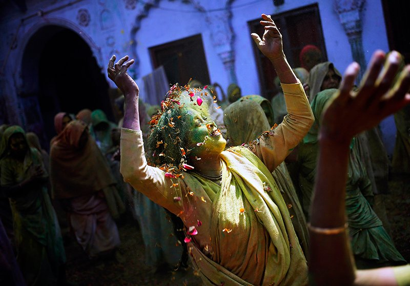 A widow daubed in colors dances as she takes part in the Holi celebrations organized by non-governmental organization Sulabh International at a widows' ashram at Vrindavan in the northern Indian state of Uttar Pradesh March 4, 2015. Photo courtesy of REUTERS/Anindito Mukherjee  *Editors: This photo can only be published with RNS-HOLI-COLORS, originally published on March 4, 2015.