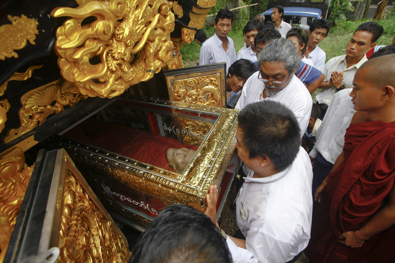 Former movie star Kyaw Thu, center with glasses, chairman and founder of Yangon's Free Funeral Services Society, helps to place the body of famous Buddhist monk Bhadanta Kovida into a hearse at Nyein Chan Yae (Peace) monastery in Yangon June 25, 2011. Photo courtesy of REUTERS/Soe Zeya Tun  *Editors: This photo can only be republished with RNS-MYANMAR-CREMATION, originally transmitted on March 2, 2015.