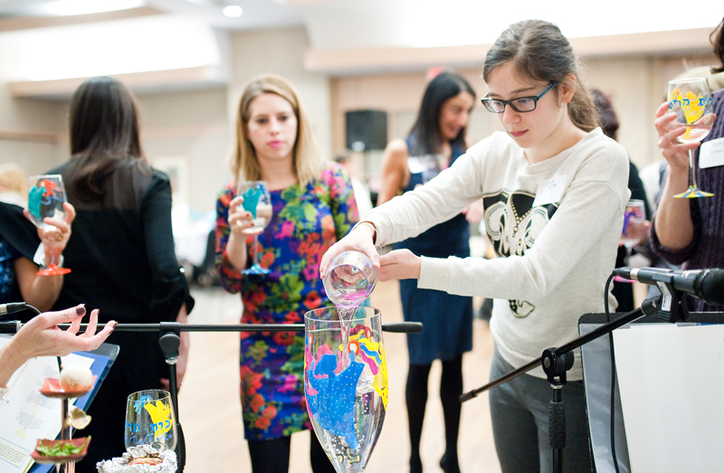 Sabrina Miller, right, fills up a Miriam's Cup during the sisterhood/zhava annual women's seder at Congregation Beth El of Montgomery County in Bethesda, Md., on Sunday, March 22, 2015. Religion News Service photo by Sait Serkan Gurbuz