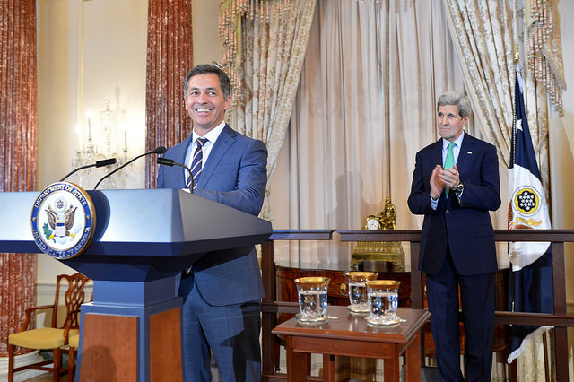 With U.S. Secretary of State John Kerry looking on, Randy Berry, the first-ever Special Envoy for the Human Rights of LGBT Persons, delivers remarks at a welcome reception in Special Envoy Berry's honor at the U.S. Department of State in Washington, D.C., on February 28, 2015.