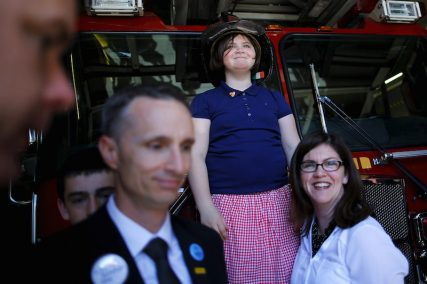 Jane Richard, the sister of Boston Marathon bombing victim Martin Richard, tries on a firefighters's helmet during a visit to the fire station on Boylston Street on the second anniversary of the Boston Marathon bombings in Boston. With her are her father Bill (left) and mother Denise (right).  Photo by REUTERS/Brian Snyder.
