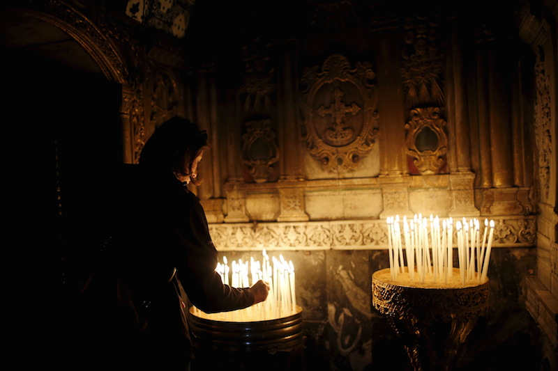An Armenian woman lights a candle during a mass marking the 100th anniversary of the mass killings of 1.5 million Armenians by Ottoman Turkish forces, in Jerusalem's Old City April 24, 2015.  Photo courtesy REUTERS/Amir Cohen.  *Eds: This photo can only be used with RNS-TRAUBE-COLUMN, transmitted April 24, 2015.