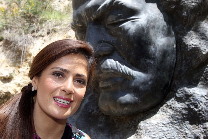 "Actress Salma Hayek stands near a statue of late writer Khalil Gibran during a visit to promote her film ""The Prophet"" in Gibran's hometown of Bcharre, Lebanon."