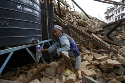 A man fills water from a water tank near a collapsed temple in Kathmandu, Nepal.