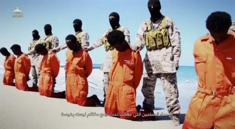 Islamic State militants stand behind what are said to be Ethiopian Christians along a beach in Wilayat Barqa, in this still image from an undated video made available on a social media website on April 19, 2015. REUTERS/Social Media Website via Reuters.