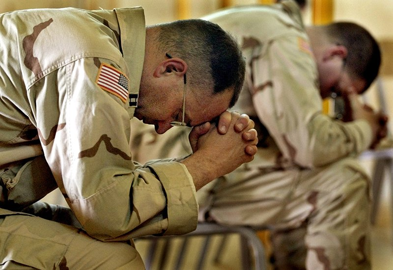 United States Army Chaplain Tim Meader, left, and Chaplain William Lovell, both from Fort Carson, Colorado, bow their heads in prayer during an Easter service at Camp New Jersey, in Kuwait on April 20, 2003. Photo courtesy of REUTERS/Adrees Latif *Editors: This photo may only be republished with RNS-ARMY-CHAPLAINS, originally transmitted on April 9, 2015.