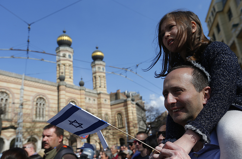 """A man with his daughter on his shoulders holds an Israeli flag as they participate in the annual """"March of the Living"""" to commemorate the deaths of around half a million Hungarian Jews during the Holocaust in World War Two, in Budapest on April 12, 2015. Photo courtesy of REUTERS/Laszlo Balogh *Editors: This photo may only be republished with RNS-HOLOCAUST-IRAN, originally transmitted on April 14, 2015."""