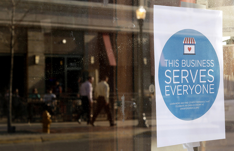 """A sign reading """"This business serves everyone"""" is placed in the window of Bernadette's Barbershop in downtown Lafayette, Indiana on March 31, 2015. The store is one of several who display a sticker stating """"This business serves everyone.""""  Indiana's Republican Governor Mike Pence, responding to national outrage over the state's new Religious Freedom Restoration Act, said on Tuesday he will """"fix"""" it to make clear businesses cannot use the law to deny services to same-sex couples. Photo courtesy of REUTERS/Nate Chute"""