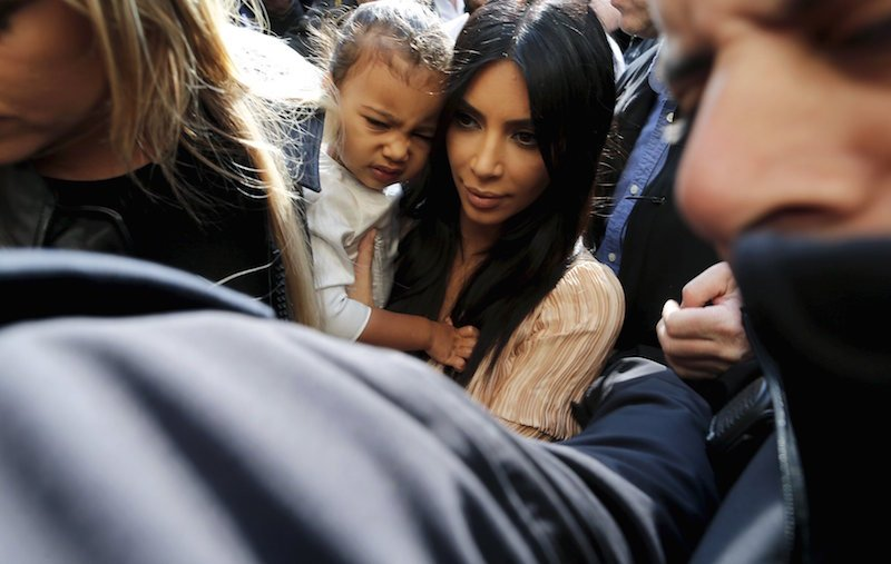 U.S. reality TV star Kim Kardashian holds her toddler daughter North West as they arrive for a baptism ceremony at the Cathedral of Saint James in Jerusalem's Old City April 13, 2015. Photo courtesy of REUTERS/Ammar Awad.
