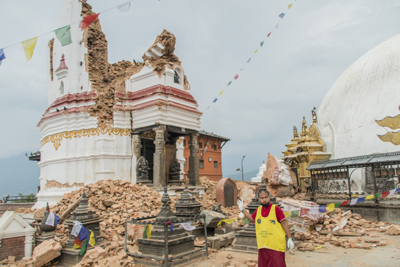 A volunteer stands in front of a collapsed temple at the Swayambhunath temple complex in Nepal. Religion News Service photo by Vishal Arora