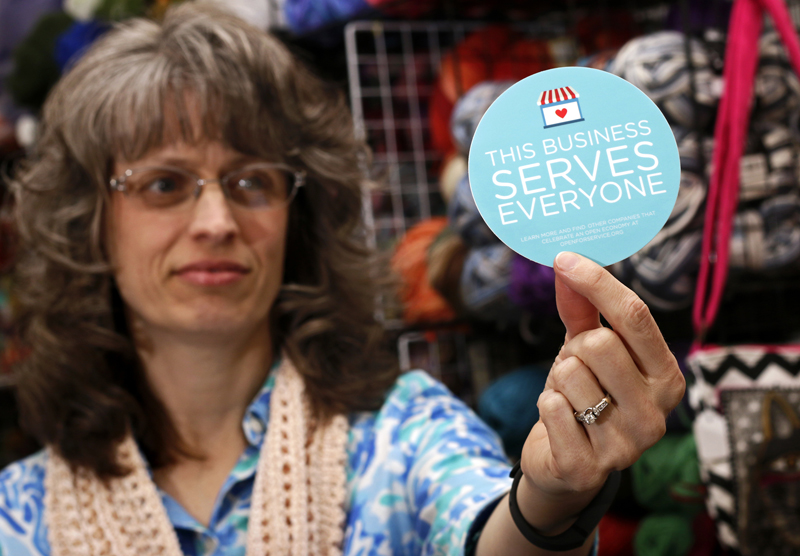 "Elizabeth Ladd, owner of River Knits Fine Yarns, poses while holding up a ""This businesses serves everyone"" sticker she plans to place outside her business in downtown Lafayette, Indiana on March 31, 2015. Photo courtesy of REUTERS/Nate Chute *Editors: This photo may only be used with RNS-POLLS-INDIANA, originally transmitted on April 2, 2015."