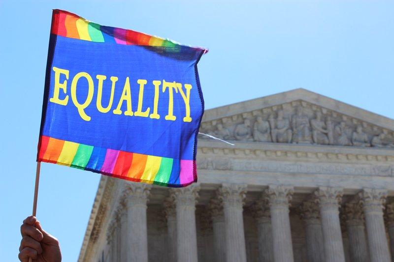 "An ""Equality"" flag waves against the sky as crowds gathered in front of the Supreme Court on April 28, 2015 as justices heard arguments about same-sex marriage. Religion News Service photo by Adelle M. Banks"