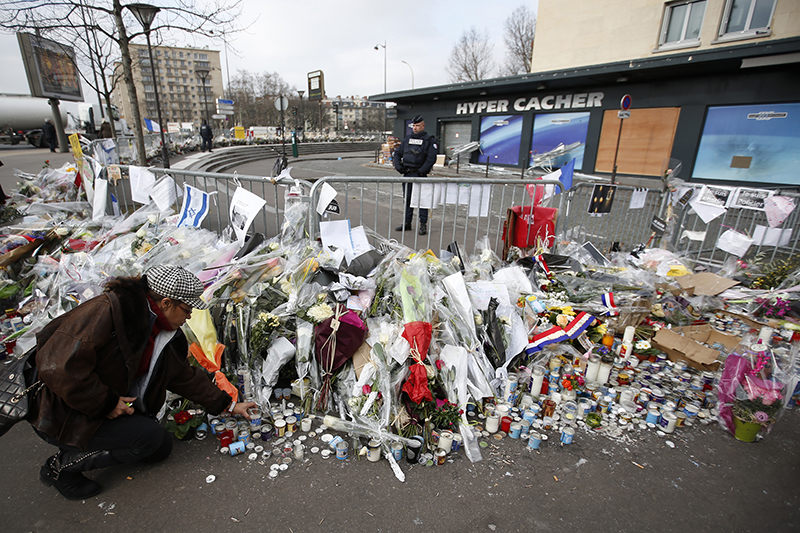 A woman lights candles in front of the Hyper Cacher kosher supermarket at the Porte de Vincennes in Paris on January 21, 2015. Four people were killed in a hostage-taking situation during an attack by an Islamist militant on January 9, 2015. Photo courtesy of REUTERS/Charles Platiau Editors: This photo may only be republished with RNS-SEMITISM-SPIKE, originally transmitted on April 15, 2015.