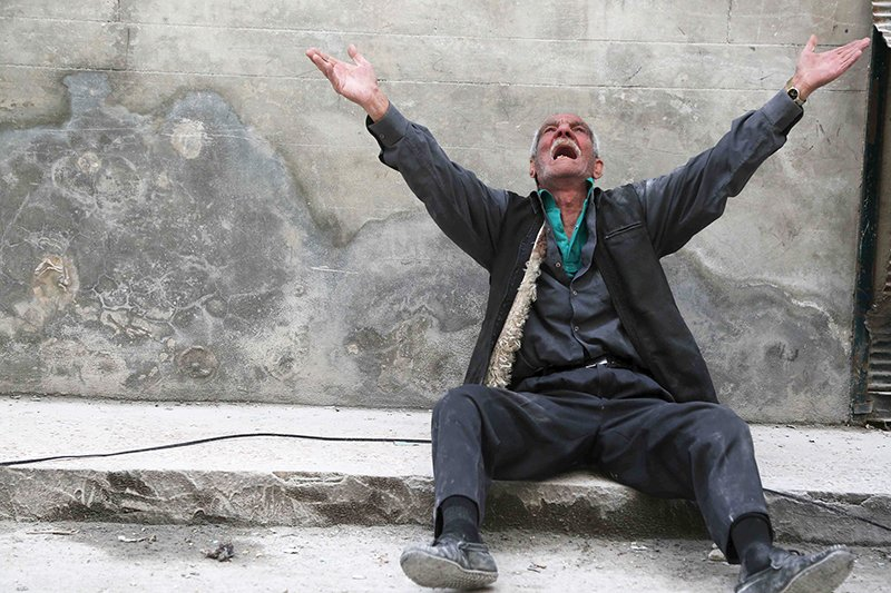 A man reacts at a site hit by what activists say was a barrel bomb dropped by forces loyal to Syria's President Bashar al-Assad, in Aleppo's al-Fardous district on April 29, 2015. Photo courtesy of REUTERS/Hosam Katan *Editors: This photo may only be republished with RNS-SYRIA-BISHOP, originally transmitted on April 29, 2015.