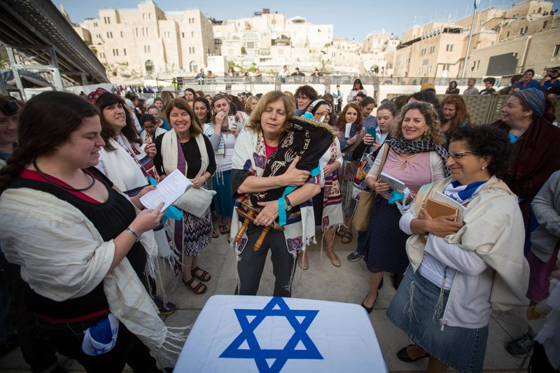 Women of the Wall, who retrieved a Torah scroll from the men's prayer section despite regulations against women reading from a Torah at the Wall, celebrate during their monthly prayer service at the Wall. Photo courtesy of Miriam Alster/Flash 90
