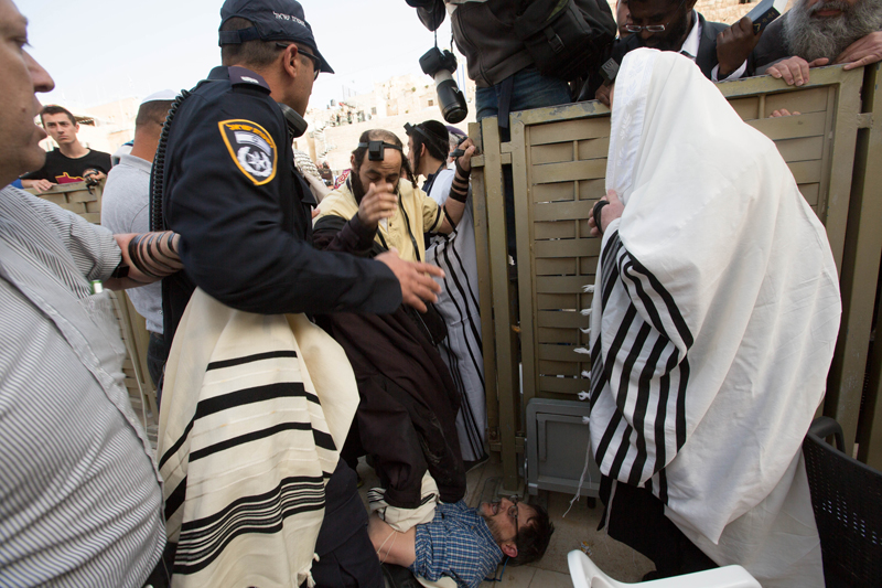 An ultra-Orthodox Jew attacks a male supporter of Women of the Wall for enabling a female worshiper to transfer a Torah from the men's section into the women's section of the Western Wall. There are no Torah scrolls on the women's section per orders of the Rabbi of the Wall. Photo courtesy Miriam Alster/Flash 90