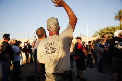 """A demonstrator waves during the """"Freedom of Speech Rally Round II"""" across from the Islamic Community Center in Phoenix, Ariz."""