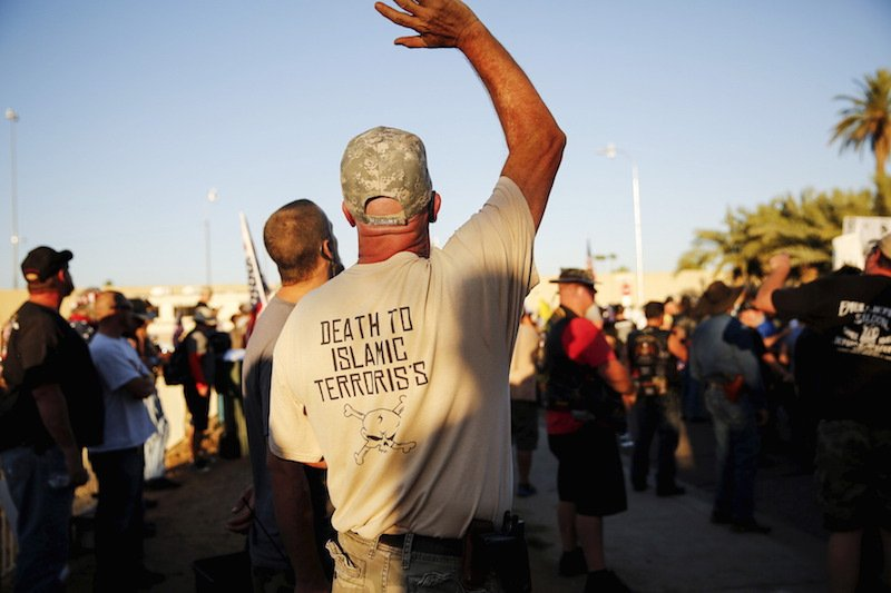 "A demonstrator waves during the ""Freedom of Speech Rally Round II"" across from the Islamic Community Center in Phoenix, Ariz."