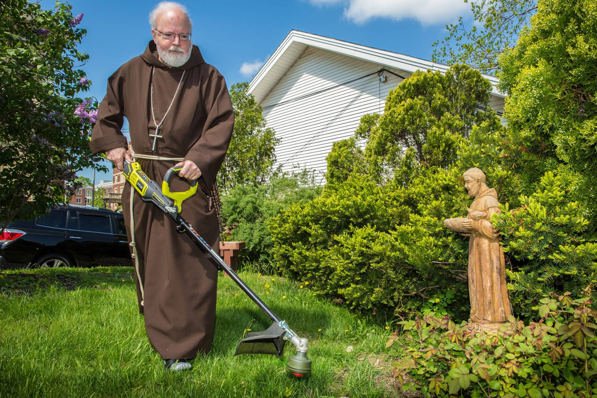 Cardinal Seán O'Malley helps out with the weed-whacking on the grounds of St. Mary of the Angels in Roxbury Monday morning as members of the Pastoral Center volunteer to refresh the grounds of several Boston area churches. Photo courtesy of George Martell/Archdiocese of Boston